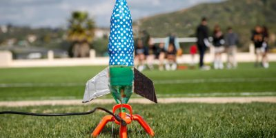 water bottle rocket colorfully decorated ready for launching with students in background against a t20 mRX2zn min
